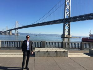 Scott Plank standing by the San Francisco bridge after working on developing The Hall SF.